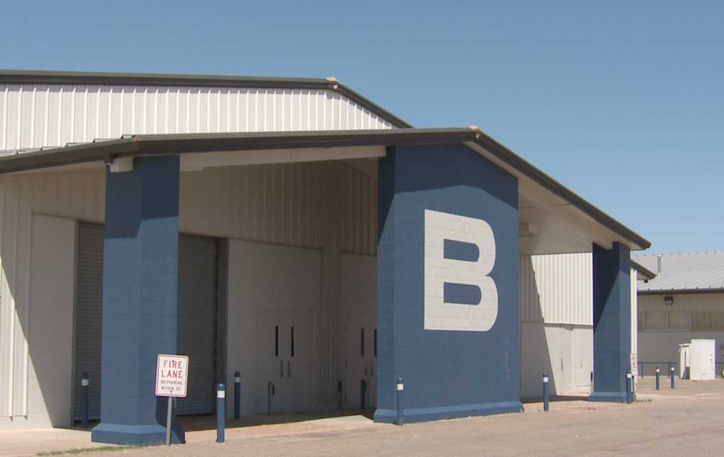 Entrance of large, white metal building with blue trim. The letter B is displayed on a middle support pillar under the front portico